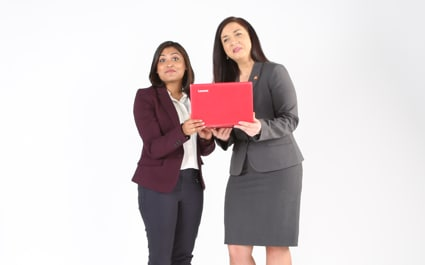 Two women holding a laptop.