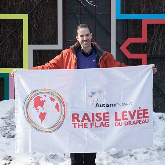 David Moloney holding an Autism Ontario flag