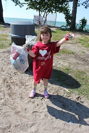 A little girl holding a bag of recycles and trash giving a thumbs up