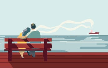 A couple sits by the waterfront watching a boat sail by.