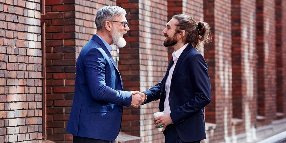 A Financial Services Representative shakes hands with a client.