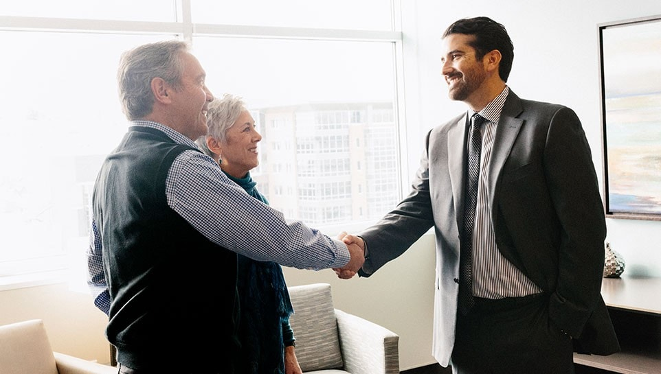 A CIBC advisor greeting a couple in his office