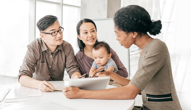 A CIBC advisor going over documents with a young family.