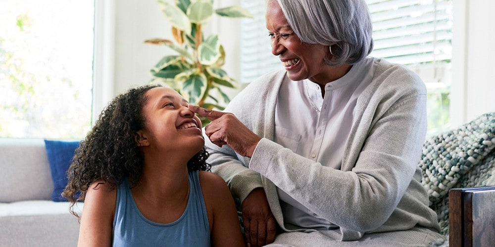 A grandmother being playful with her granddaughter