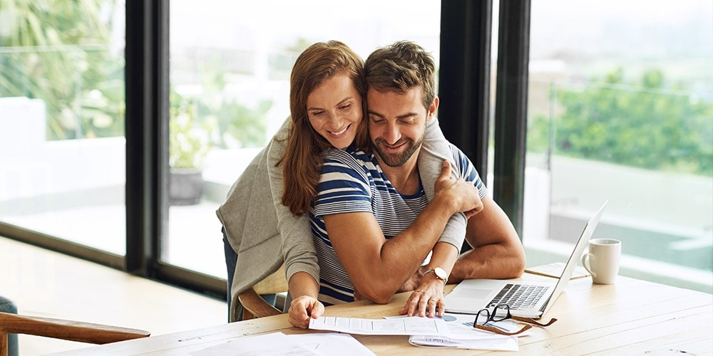 A happy couple going over financial documents