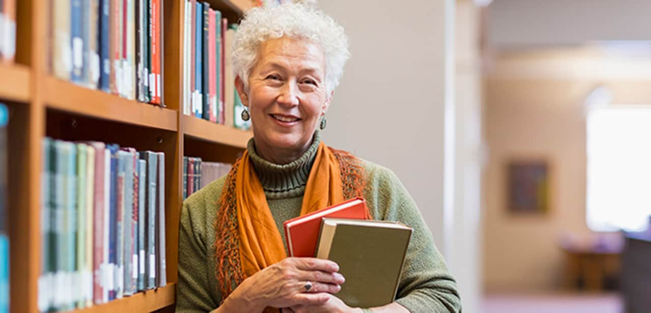 An older woman holding books at a library.