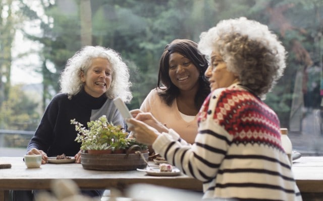 Three older women chat over breakfast.