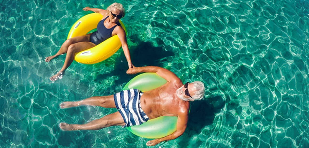 An older couple floating on inner tubes.