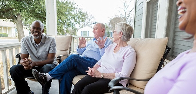 A group of retirees chatting on a porch