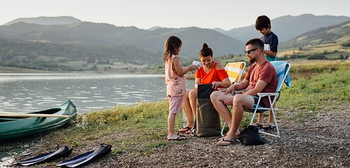 A family of 4 relaxing by a lake next to their small, beached boat.