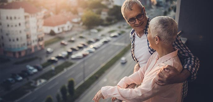 A retired couple enjoying the view from the balcony of their condo