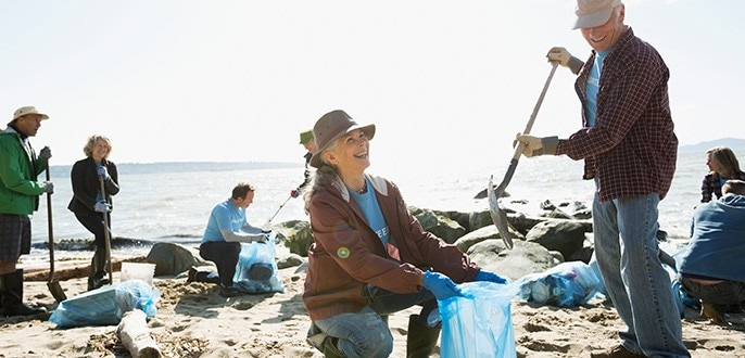 A woman cleaning up a beach.