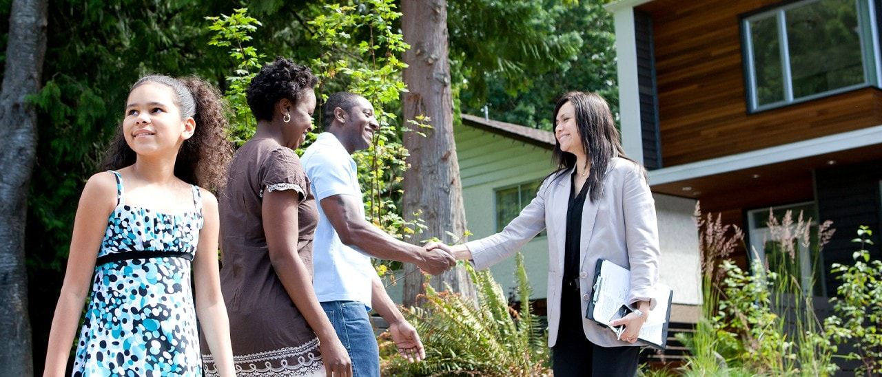 A family standing in front of a home with the husband shaking the hand of a real estate agent.