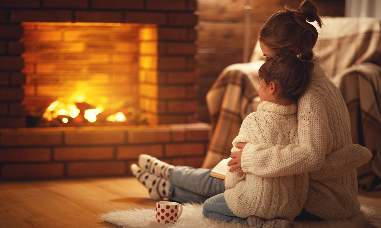 A mother and her daughter snuggled up by their fireplace