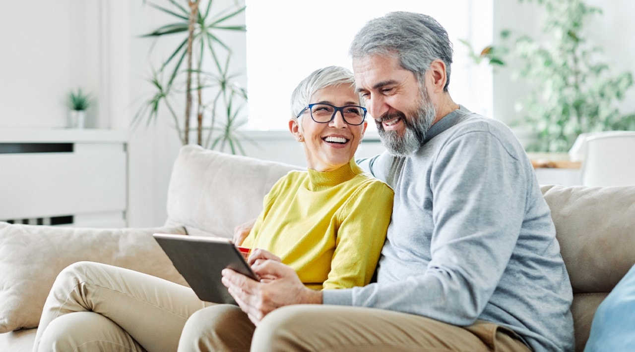 A smiling senior couple using a tablet together at home.