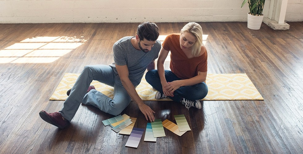 Couple sitting on the floor looking at paint samples