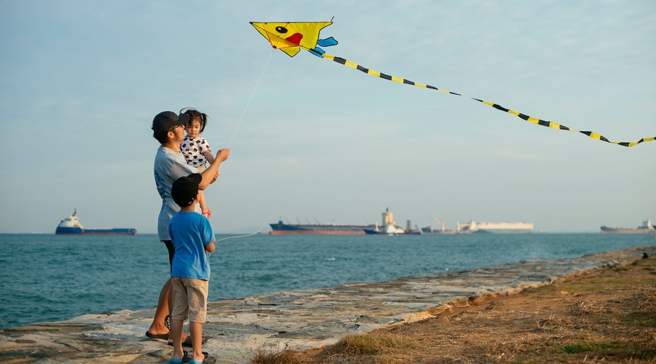 A family flying a kite on a Maritime beach.