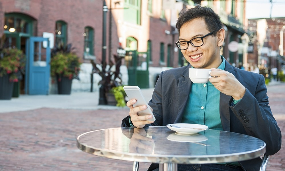 Man enjoying his coffee while reading an eStatement on his phone