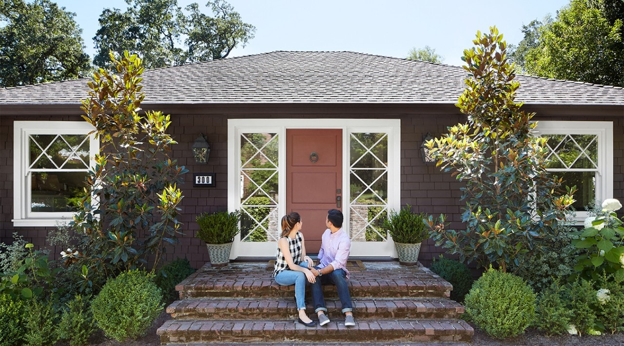 A millennial couple sits on the front steps of their home and turns to face the door.