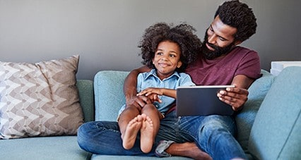 Father and son playing with a tablet together on the couch