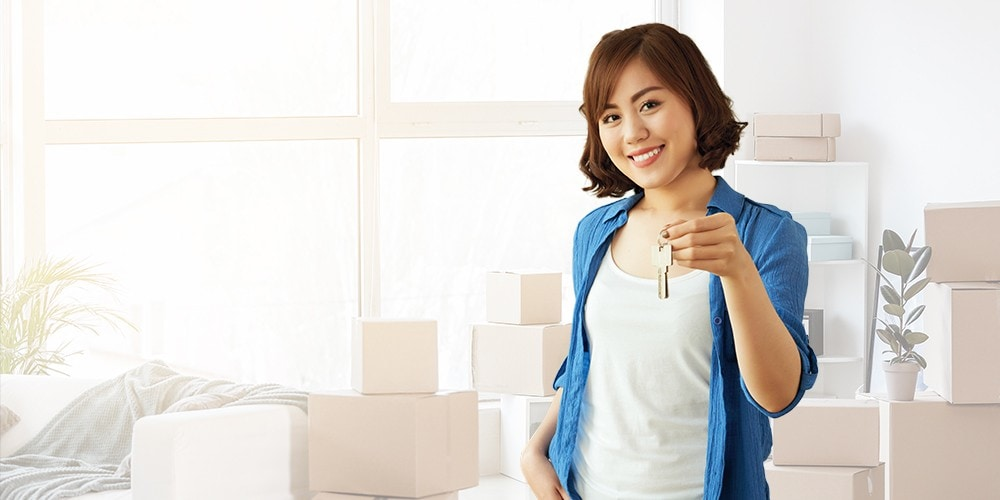 Smiling woman holds up her house keys