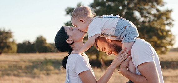 A toddler on her dad's shoulders leans over to give her mom a kiss