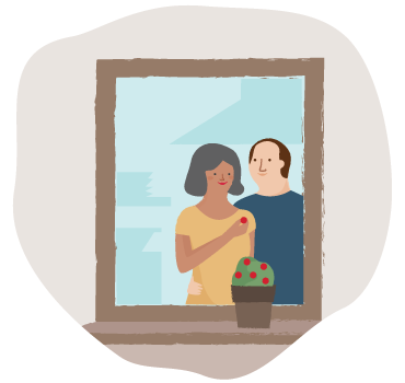 A couple staring into a mirror while the woman holds a flower