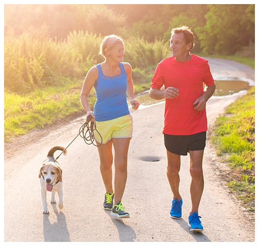 a happy couple jogging with their dog