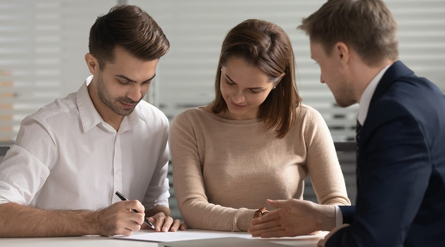 Young couple meeting with an advisor and signing documents.