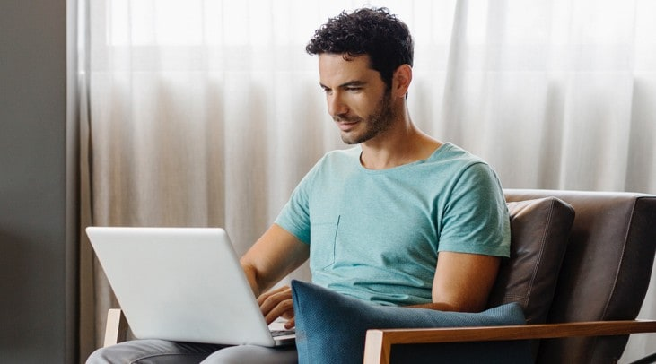 Man at home checking his investments on his laptop
