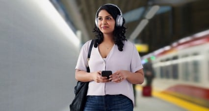 Woman with headphones on listening to music on her smartphone